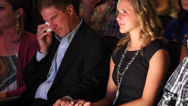 17 year-old Kendal Conney, of Camden, Mich., holds her father Shawn's hand as he wipes away tears while watching a short documentary on why she was nominated for a $25,000 scholarship from Sallie Mae. Coney was amongst the four high school students from across the country were individually awarded the  25,000 scholarship Tuesday afternoon.