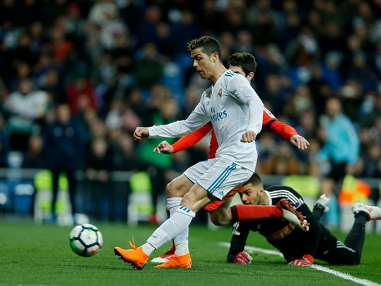 Real Madrid's Cristiano Ronaldo, left, scores past Real Sociedad's goalkeeper Geronimo Rulli, on the ground right, during a Spanish La Liga soccer match between Real Madrid and Real Sociedad at the Santiago Bernabeu stadium in Madrid, Saturday, Feb. 10, 2018. Ronaldo scored a hat-trick in Real Madrid's 5-2 victory. (AP Photo/Francisco Seco)