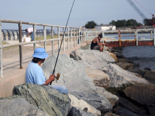 Raul Arellano of Wilmington waits for a fish to bite while sitting on the rocks at the Indian River Inlet.