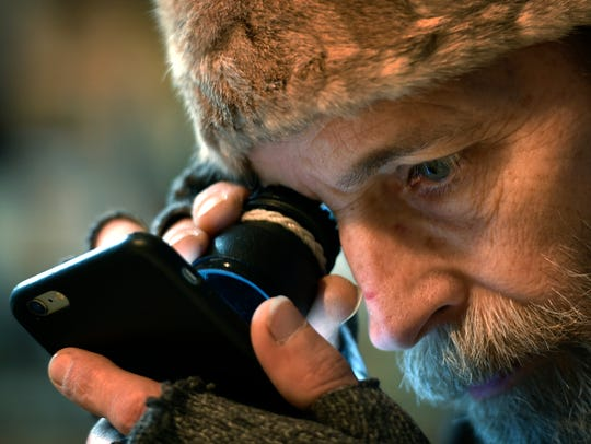 Jimmy Abegg uses a photo loupe to read text messages