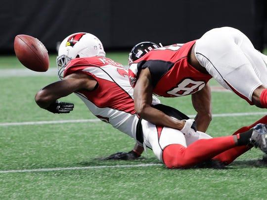 Falcons receiver Taylor Gabriel (right) hits Cardinals