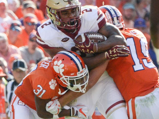 Clemson defensive back Ryan Carter (31), left, and safety Tanner Muse(19) tackle Boston College running back AJ Dillon (2) during the third quarter in Memorial Stadium at Clemson on Saturday.
