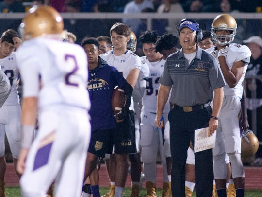 Male head football coach Chris Wolfe yells instructions to Male quarterback Cameron Chesher. 
