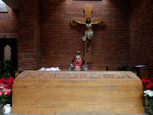 Vivian Hurmoz of Troy, Mich., kneels and prays at the tomb of Father Solanus Casey just outside of the Solanus Casey Center church in Detroit.