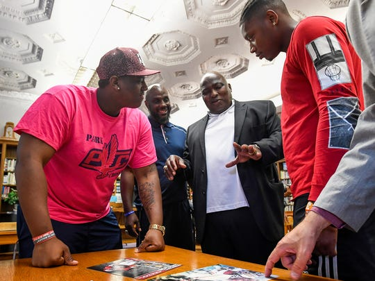 Former Lanier High School, University of Alabama and professional football player Johnny Davis, second from right, chats with Tank Jenkins, from left, Lanier football coach Marvin Cunningham and James Foster at the Lanier campus in Montgomery, Ala., on Thursday May 17, 2018.