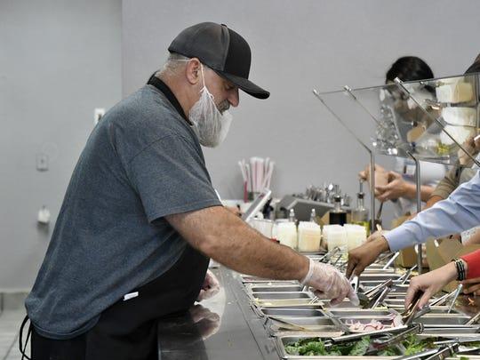 The Salad Shop co-owner John Lawson refills salad toppings during the lunch rush on Tuesday, July 3, 2018.