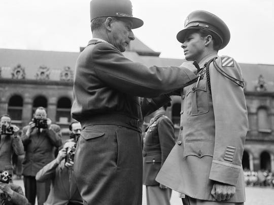 Lt. Audie Murphy, America's most decorated soldier of World War II, received the French Legion of Honor and the Croix De Guerre with palms from General De Lattre de Tassigny in the Invalides, Paris July 16, 1948.