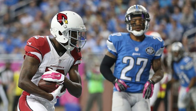 John Brown of the Arizona Cardinals scores a second-quarter touchdown in front of Glover Quin, right, of the Detroit Lions on Oct. 11, 2015, at Ford Field in Detroit.