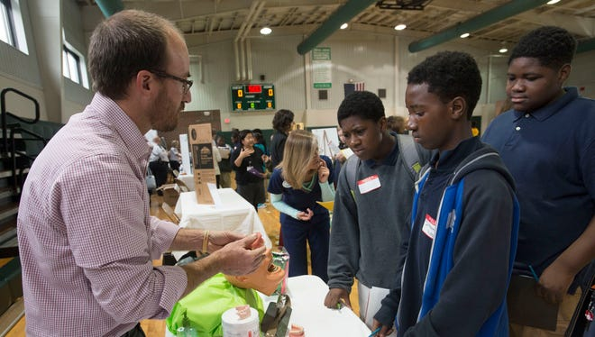 Dr. Chad Callahan, left, talks to Warrington Middle School students in December 2015 about exploring careers in dentistry and orthodontics during a Career Day.