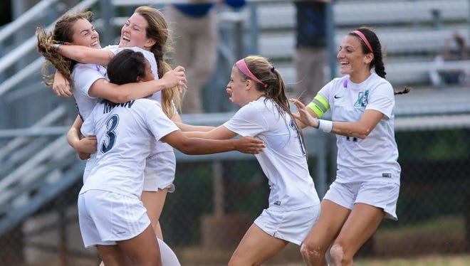J.L. Mann players celebrate a goal by Caroline Conti, far left, during the Patriots' 3-0 win over Fort Mill Monday night in the Class AAAA Upper State final.