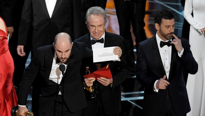 'La La Land' producer Jordan Horowitz (L) holds up the winner card reading actual Best Picture winner 'Moonlight' after a presentation error with actor Warren Beatty and host Jimmy Kimmel onstage during the 89th Annual Academy Awards at Hollywood & Highland Center on February 26, 2017 in Hollywood, California.