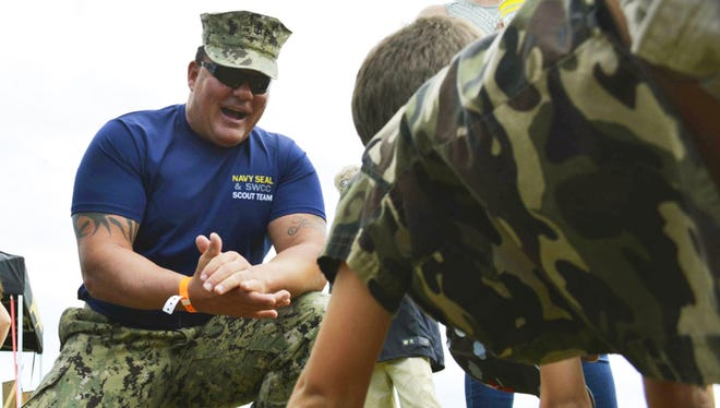 This Nov. 6, 2016, photo provided by the U.S. Navy shows Chief Petty Officer Joseph Schmidt III, assigned to the Navy SEAL and SWCC Scout Team, encouraging a young fan to do pushups at the 2016 Stuart Air Show in Stuart, Fla. The Navy is investigating Schmidt, a decorated SEAL who moonlights as a porn actor.