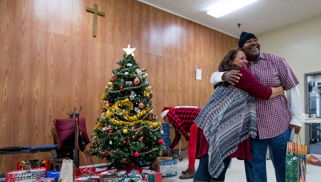 Tammy Middleton, executive director of the Friendship Mission, left, hugs Ron Smith as she hands out gifts during the Friendship Mission Christmas Party at the homeless shelter in Montgomery, Ala. on Thursday December 14, 2017.