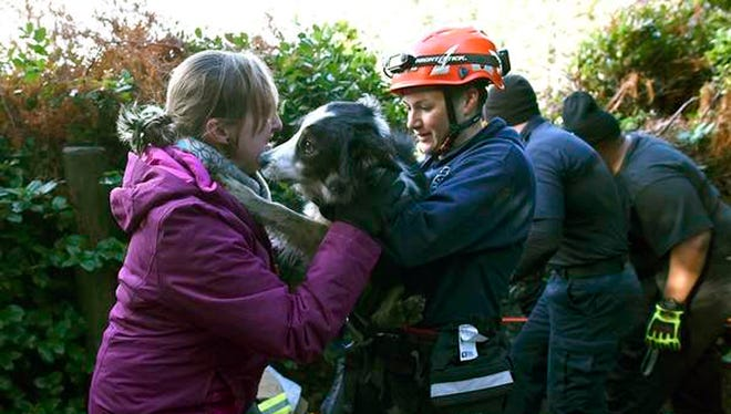 In this Tuesday, Dec. 26, 2017, photo, Sarah Stremming, left, is reunited with her dog, Felix, after he was rescued from a precipice north of Indian Beach in Ecola State Park.