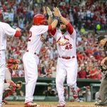 Matt Holliday of the Cardinals, second from right, celebrates with teammates Matt Carpenter, left, and Jeremy Hazelbaker after his first-inning home run on Friday in St. Louis.