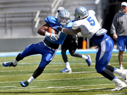 MTSU's Shane Tucker gets tackled by Jeremiah Bryson during MTSU's first scrimmage of the season on Saturday April 4, 2015.