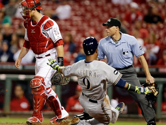 Milwaukee Brewers' Jean Segura (9) scores on a sacrifice fly by Kyle Lohse while Cincinnati Reds catcher Devin Mesoraco waits for the ball in the eighth inning of a baseball game, Wednesday, Sept. 24, 2014, in Cincinnati. Milwaukee won 5-0. Home plate umpire Dan Iassogna watches the play. (AP Photo/Al Behrman)