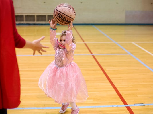 Allison Bradley, 2, of Dover, throws the ball to her mom, Sara Bradley, after the costume contest at YMCA in York Thursday, October 25, 2012.  DAILY RECORD/SUNDAY NEWS - KATE PENN