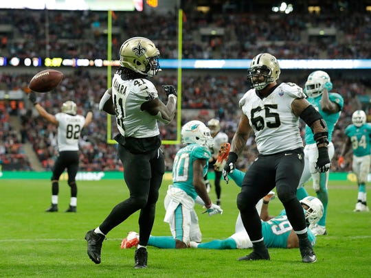New Orleans Saints running back Alvin Kamara (41) celebrates with offensive guard Senio Kelemete (65) after scoring a touchdown during the second half of an NFL football game against the Miami Dolphins at Wembley Stadium in London, Sunday Oct. 1, 2017. (AP Photo/Matt Dunham)
