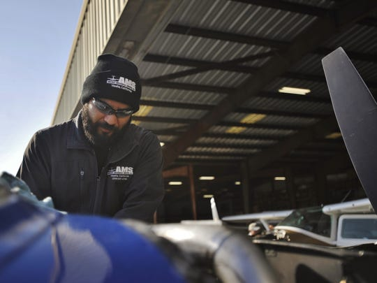 Chris Munoz works on Bob Christopher's plane that had mechanical issues while flying over Visalia Wednesday morning.