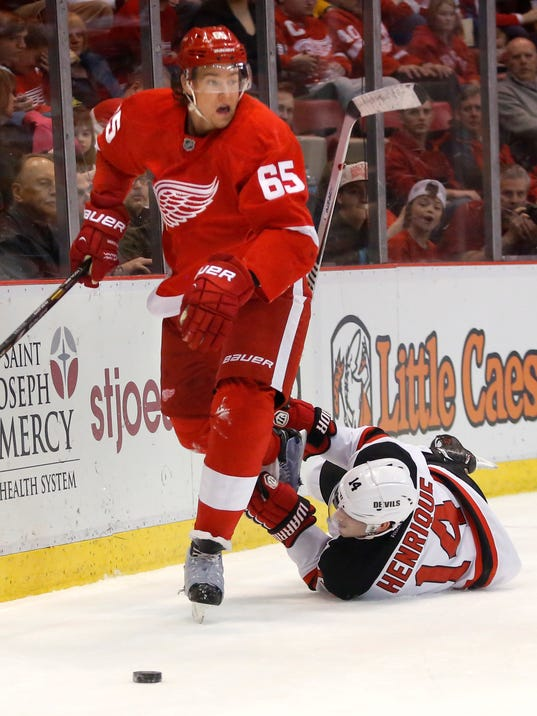 New Jersey Devils' Adam Henrique (14) tries to trip up Detroit Red Wings' Danny DeKeyser (65) during the first period of an NHL hockey game Friday, March 7, 2014, in Detroit. (AP Photo/Duane Burleson)