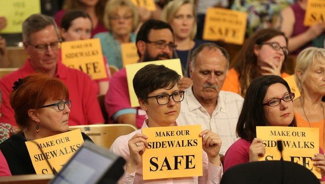 Members in the gallery for Wednesday afternoon's Metro Council Public Safety Committee meeting hold up signs wanting a larger buffer for patients at EMW Women's Surgical Facility. June 14, 2017