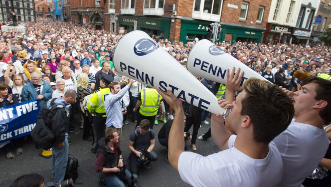 Thousands of Penn State fans take part in a pep rally at Temple Bar in Dublin, Ireland, Friday, Aug. 29, 2014. Penn State plays UCF in a football game Saturday. (AP Photo/PennLive.com, Joe Hermitt)