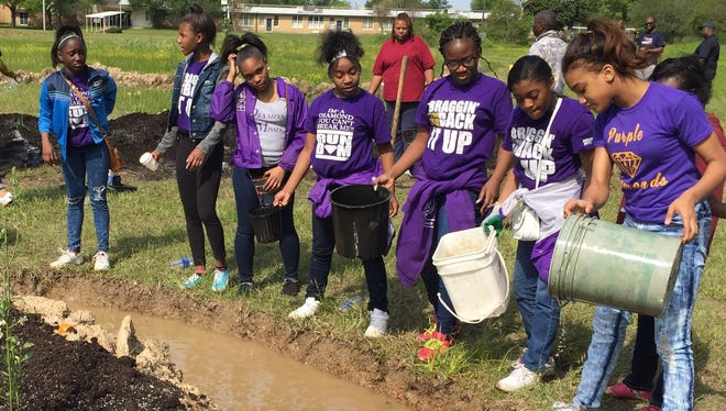 Members of the Purple Diamonds dance team fill a swale at the Rosemont Community Orchard in Jackson.