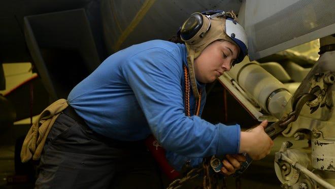 U.S. Navy Aviation Botswain's Mate (Handling) Airman Samantha Clift, a native of San Angelo,chains down an aircraft in the hangar bay aboard the aircraft carrier USS Nimitz (CVN 68).