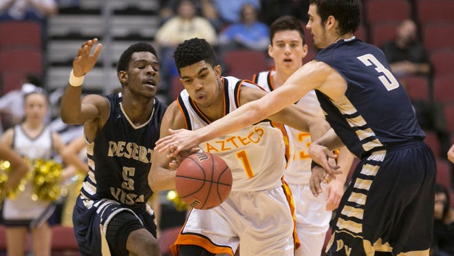 Corona del Sol's Tyrell Henderson breaks through a double team of Desert Vista's Quincy Taylor (left) and David Powell during the Division I championship game at Gila River Arena in Glendale on March 2, 2015.