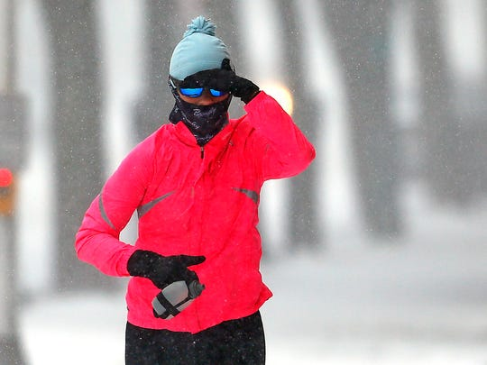 Melissa Archuleta of Morristown covers her face as she runs down South Street in Morristown through heavy snow and strong winds from a blizzard sweeping through New Jersey on Thursday morning that could bring up to a foot of snow to parts of the state while Morris County is expected to get only 2 to 4 inches.  January 4, 2018. Morristown, NJ.