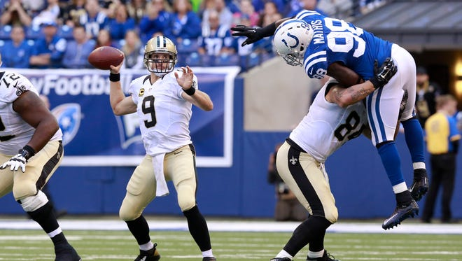 Indianapolis Colts outside linebacker Robert Mathis (98) is blocked by New Orleans Saints tight end Michael Hoomanawanui (84) to allow quarterback Drew Brees (9) time to throw in the second half of an NFL football game on Oct. 25 in Indianapolis. The Saints defeated the Colts 27-21.