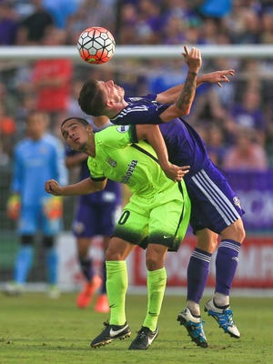 Louisville City's Nial McCabe bends over to head the ball against Charleston's Ataulla Guerra. The match ended in a draw, 1-1.