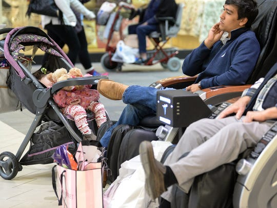 Josie Stancil, left, naps near her uncle Grant Dye of Toccoa, relaxing in a chair after shopping at the Anderson Mall during Black Friday in Anderson.