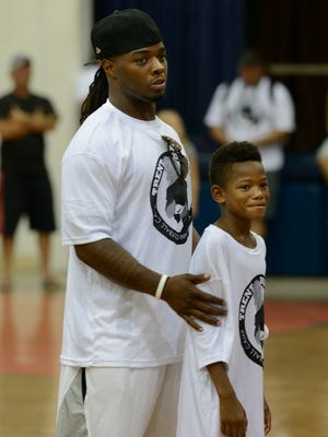 Trent Richardson of the Oakland Raiders, gives kids a pep talk with Ricky Johnson by his side Saturday during the Trent Richardson Football Camp at Escambia High School.