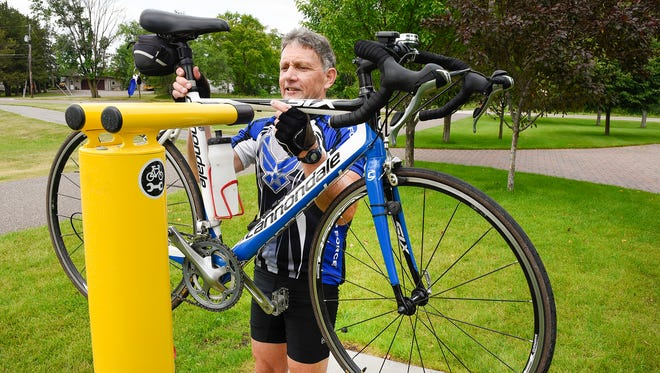 Bob Klackner lifts his bike onto one of the new bike repair stations along the Lake Wobegon Trail Thursday, June 28, in St. Joseph. The seven service stations located along the trail have basic bike tools and a tire pump. Also on the stations are a QR code you can scan on a smart phone to get instruction on basic bike repairs.