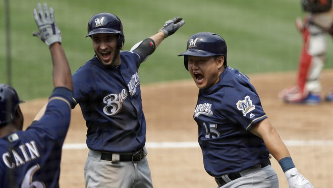 Ji-Man Choi (right) celebrates his grand slam on Saturday against the Phillies with Ryan Braun and Lorenzo Cain.