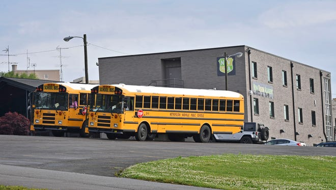Buses sit in the parking lot of New Vision Academy, which is under federal and state investigations.