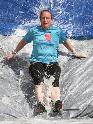 D.A. Hernandez of Dundee slides down a slippery ramp into a pool of cool water. She was part of the first group of Forge Through Hell 5K participants Saturday at Hell Survivors in Pinckney.