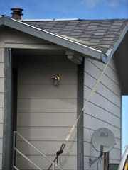 A tie-down strap helps keep the roof in place on a house in Heart Butte where the wind is a constant factor in the everyday life of residents.
