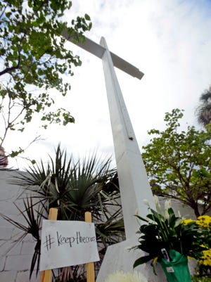 """Signs stand on Sunday, June 25, 2017, at the foot of the cross at Bayview Park in Pensacola during the """"Save the Cross Service."""" Echo Life Church, along with First City Church and Legacy House Church, came together for the religious service."""