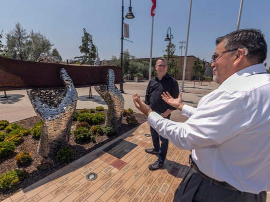 """ADVANCE FOR USE SUNDAY, SEPT. 11, 2016 AND THEREAFTER-In this Friday, Aug. 26, 2016 photo, California State EDD employee Juan Milan, right, talks with artist Heath Satow about his sculpture, """"Reflect,"""" made with a damaged, rusted I-beam from the collapsed World Trade Center buildings, outside the Rosemead, Calif., city hall plaza. Satow said he purposely positioned the beam at about eye level, so people could see, touch and feel it. (AP Photo/Damian Dovarganes)"""