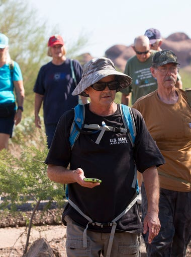 """Bill Sweet, of Mesa, and Don Shrum, of Scottsdale, demonstrates how geocaching, a high-tech treasure hunt using GPS devices, is played in Papago Park in Phoenix on Friday, September 11, 2015.  They hunt for """"Picture This-Sleeping Alien"""" cache."""