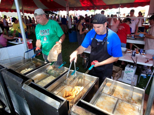 Geno Fidler, left, and Joe Eernisse fry shrimp and cod at a previous Port Fish Day. The popular event was canceled this year due to the coronavirus.