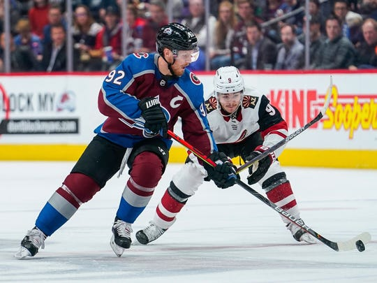 Colorado Avalanche left wing Gabriel Landeskog (92) moves the puck against Arizona Coyotes center Clayton Keller (9) during the first period of an NHL hockey game, Saturday, Oct. 12, 2019, in Denver. (AP Photo/Jack Dempsey)