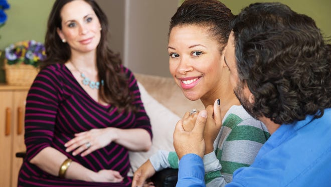 A married couple sits with their surrogate.