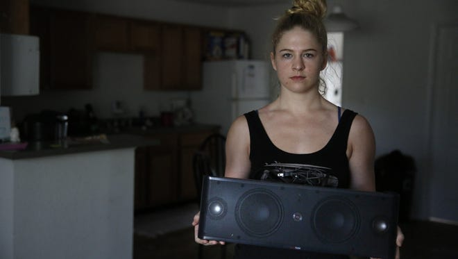 Emily Swan holds a speaker she says was fried by power surges in her apartment at the Dwell Tallahassee student living complex on West Pensacola Street Monday. Along with the other tenants in their building, Swan has been without power for a week.