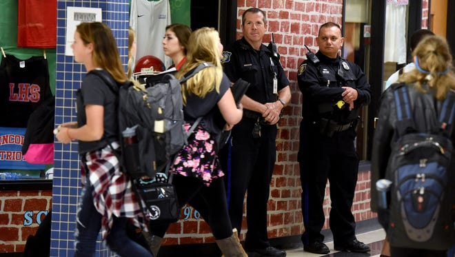 Robert Draeger and Jason Larsen School Safety Officers with Sioux Falls Police Department monitor the halls at Lincoln High School on Thursday afternoon.