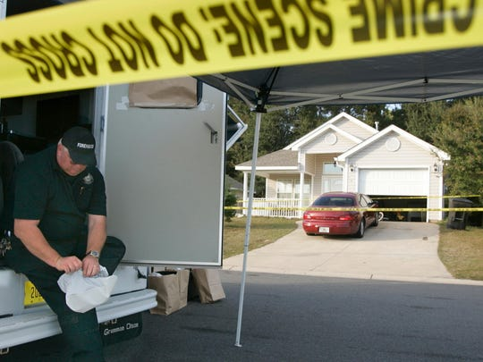 Vernon Henderson, with TPD's forensic unit, puts on a protective boot before entering the crime scene at 908 Saddle Creek Run (background), Nov. 19, 2010.