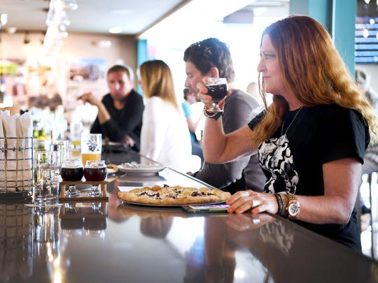 Christena Clark enjoys a beer and pizza at White Labs Kitchen and Tap October 20, 2017.